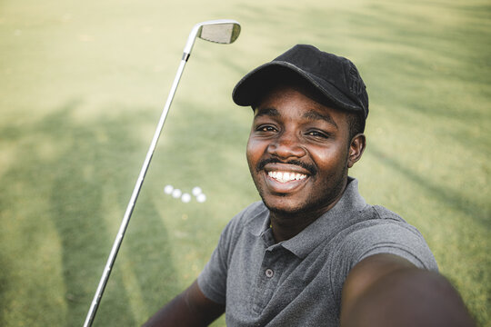 African American of young man and happy making selfie photo while standing together with golf putters during a game on the golf course.