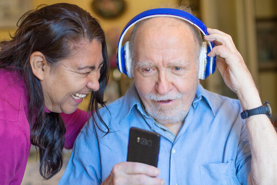 Smiling senior man and caregiver with smartphone are listening music with headphone