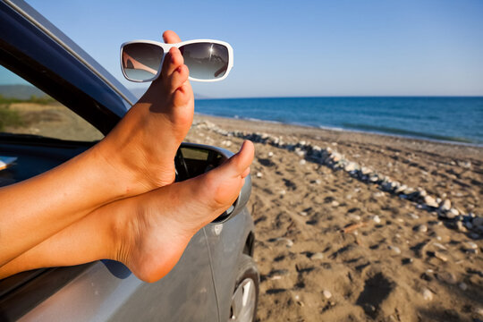 Sticking your feet out of the car by sea. Sunglasses.