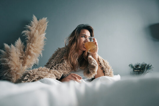 Young Woman Drinking Herbal Tea While Sitting On Bed Against Wall