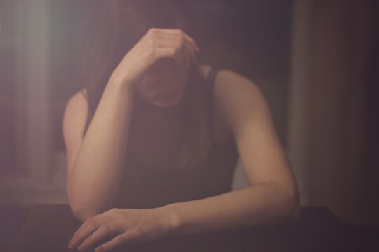 Young Depressed Woman With Head In Hand Sitting At Home