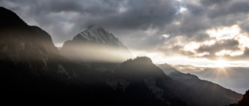 Sunlight Streaming Through Clouds Over Silhouette Mountains