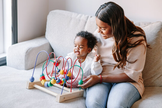 Happy smiling mixed race Indian mother and African black baby toddler playing developmental wooden bead maze toy game together at home. Authentic candid lifestyle with infant kid child.
