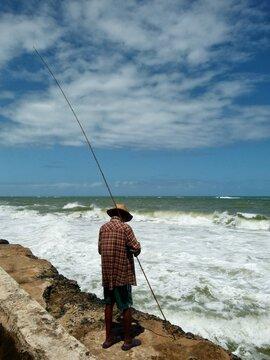 Rear View Of Fisherman Fishing In Sea