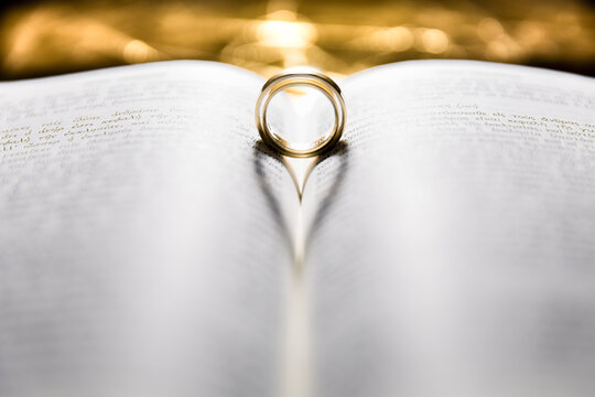 Wedding rings creating shape of the heart with Bible