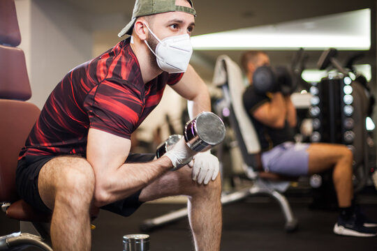 Young men working out wearing face mask & latex rubber gloves,performi