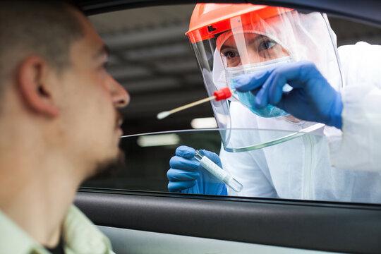 Medical UK NHS worker performing drive-thru COVID-19 test,taking nasal
