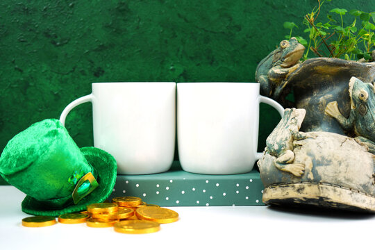 Happy St Patrick's Day two white coffee mugs, styled with leprechaun hat, shamrocks, and chocolate gold coins, on a textured green background. Mockup. Copy space.