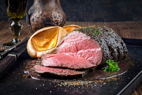 Traditional English venison roast with Yorkshire pudding and spicy sauce served as top view on a rustic tray