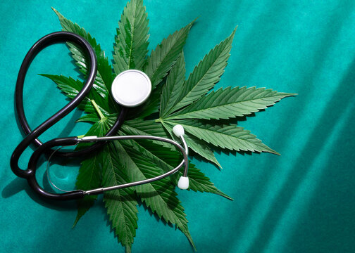 Medical marijuana cannabis cbd oil with stethoscope on green background with shades.