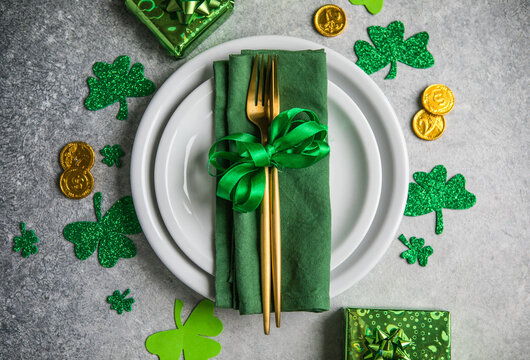 Beautiful festive table setting for St.Patricks day with cutlery and lucky symbols. Copy spase in center. Flat lay.