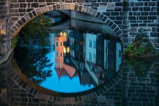 Reflection of residential houses around Pegnitz river and arch of bridge at Henkerhaus Museum, Nuremberg, Germany