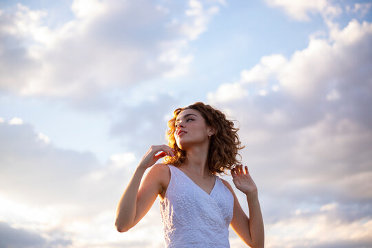 curly hair woman outdoors sky background