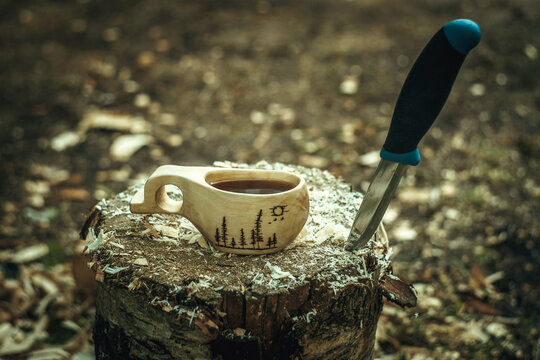 A wooden mug made of wood with black tea, next to a knife stuck in the wood. Drawing of the forest on the circle.