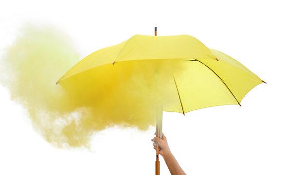 Woman holding umbrella with yellow smoke bomb outdoors, closeup