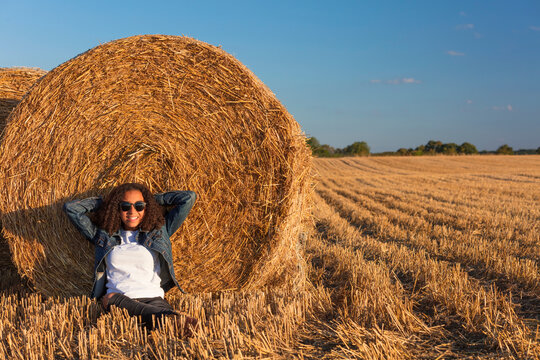 Young Woman Girl Teenager Leaning Against Hay Bale in Field at Sunset