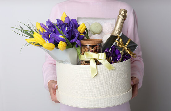 Woman holding basket with gifts, bouquet and champagne on light grey background, closeup