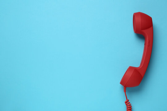 Red corded telephone handset on light blue background, top view. Hotline concept