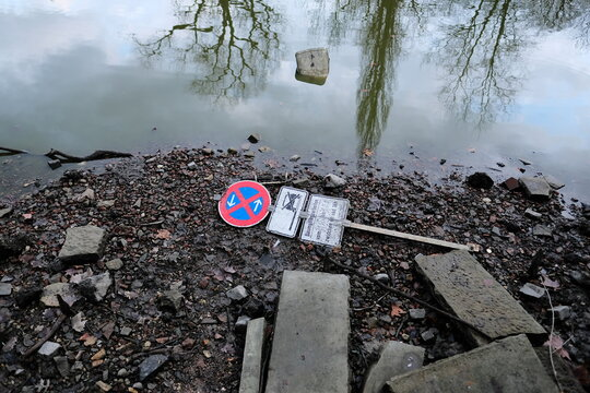 Polluted lake with garbage and road sign