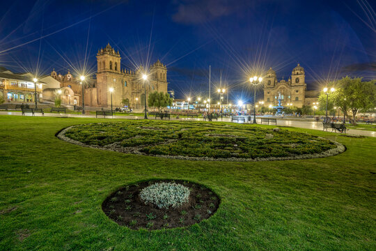 Illuminated park by Cusco Cathedral and Church of the Society of Jesus at Plaza de Armas at night, Cusco, Peru