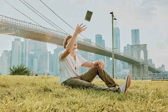 Young man sitting outdoors in park throwing phone mid air.