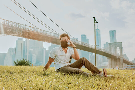 Young man sitting in park wearing face mask on phone.