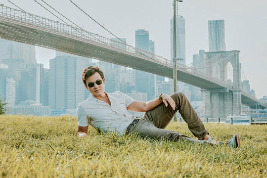Young man sitting outdoors in park wearing sunglasses.