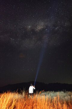 young man in the field observing the milky way with a flashlight in hi