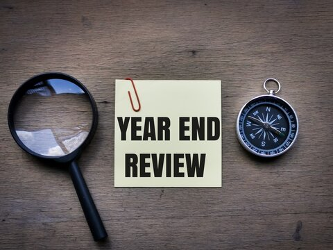 Selective focus top view text YEAR END REVIEW on sticky note with magnifying glass and compass on wooden background.