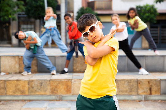 Confident tween boy hip hop dancer posing while performing with group on summer city street.