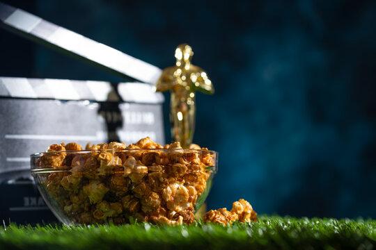 Popcorn oscar statuette and movie clapper. Screensaver for the inscription. Banner