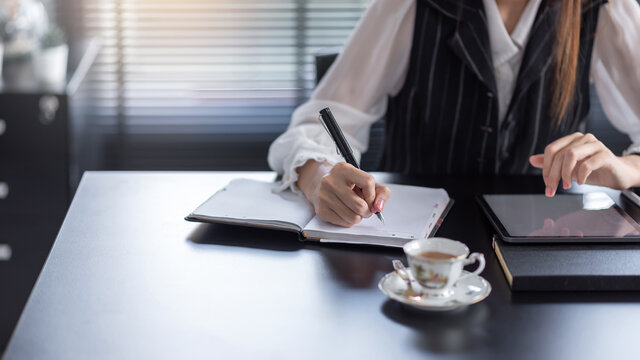 Business woman holding a pencil while taking notes with a coffee tablet at the office.