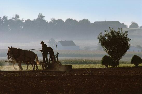 Men using horse drawn plow on Amish Farm, Lancaster, Lancaster County, Pennsylvania, USA