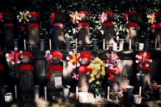 Rows of statues of Jizo Bosatsu decorated with knit caps and bibs and pinwheels to represent deceased children at a cemetery, Tokyo, Japan
