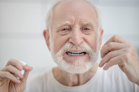 Gray-haired man in white tshirt cleaning teeth with a floss