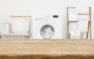 Obraz Wooden table in front of washing machine loaded with laundry - fototapety do salonu