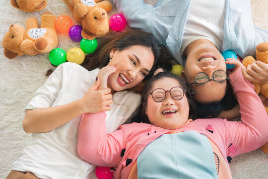 Happy Asian family laying on carpet in living room and smile with their daughter down syndrome child , a lot color balls and teddy bear dolls around them , Activity happy family lifestyle concept.