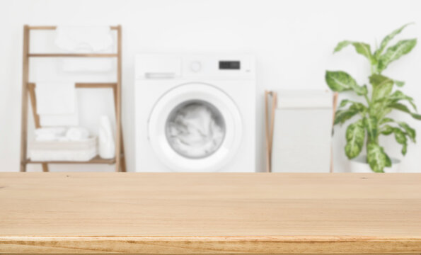 Empty wooden board over blurred laundry room washing machine background