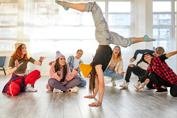 break dancer woman showing different tricks and movements while dancing in the studio, flexible and sportive female on the floor