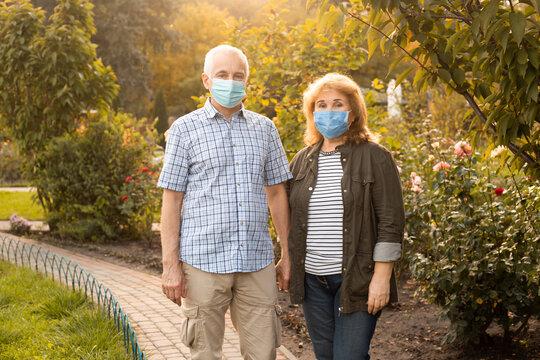 Senior couple in love wearing medical mask to protect from coronavirus outside in summer nature, coronavirus quarantine