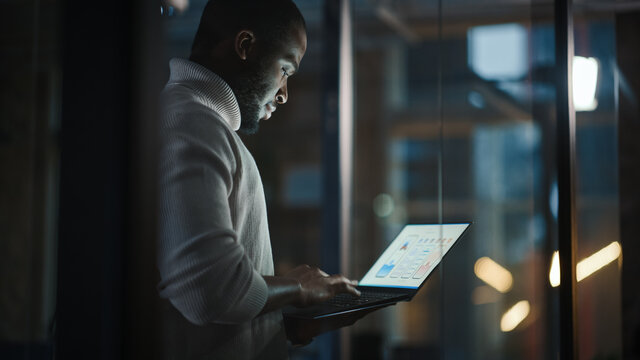 Handsome Black African American Male is Standing in Meeting Room Behind Glass Walls with Laptop Computer in an Creative Agency. Project Manager Wearing White Jumper and Working on App User Interface.