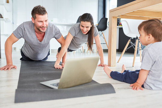 Parents do push-ups in front of the laptop computer