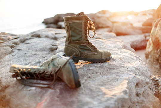 Men's army military boots with laces lie against the mountains in good weather for tourism