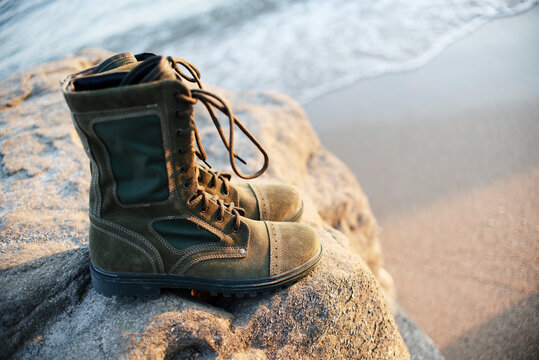 Men's army green military boots with laces stand on the background of stone and sea in fine weather