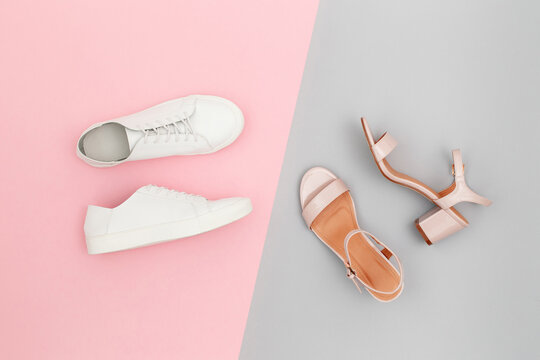 White sneakers and pink heeled sandals on grey and pink paper background. Stylish spring or summer woman's shoes in pastel colors. Trendy beauty female fashion background. Flat lay, top view.