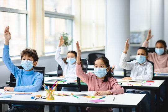 Schoolchildren raising hands at classroom, wearing medical masks