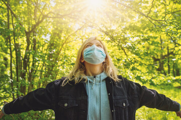 Young woman in medical face protection mask outdoors in nature.