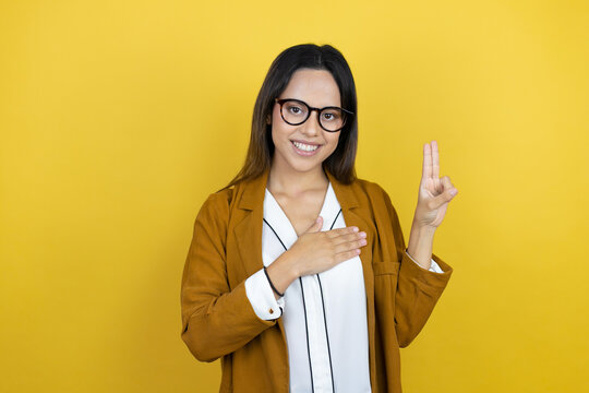 Young beautiful woman wearing a blazer over isolated yellow background smiling swearing with hand on chest and fingers up, making a loyalty promise oath
