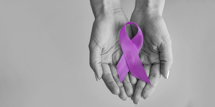 World cancer day inscription. healthcare and medicine concept - girl hands holding Purple cancer awareness ribbon. 4 february day