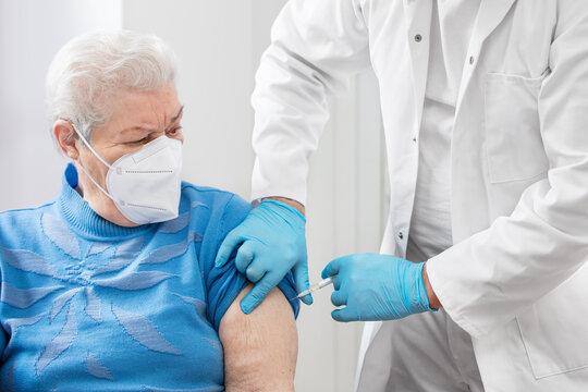 a doctor or nurse gives a senior a shot, perhaps a vaccination